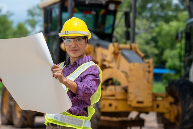 Mujeres ingeniero o arquitecto con planos con camión cargador en el sitio de construcción, vehículo de construcción de ingeniería en el área de trabajo.