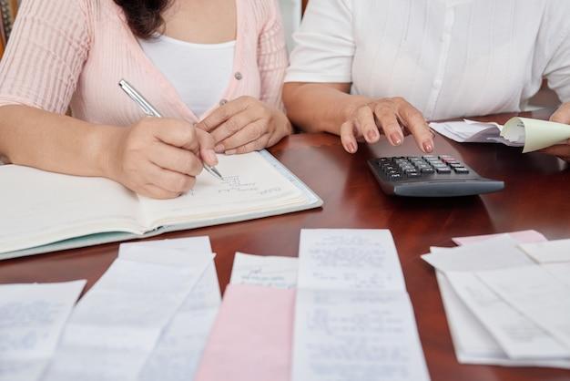 Mujeres irreconocibles sentadas a la mesa con recibos, contando con calculadora y escribiendo en diario