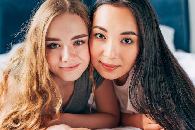 Mujeres jóvenes abrazando y mirando a cámara