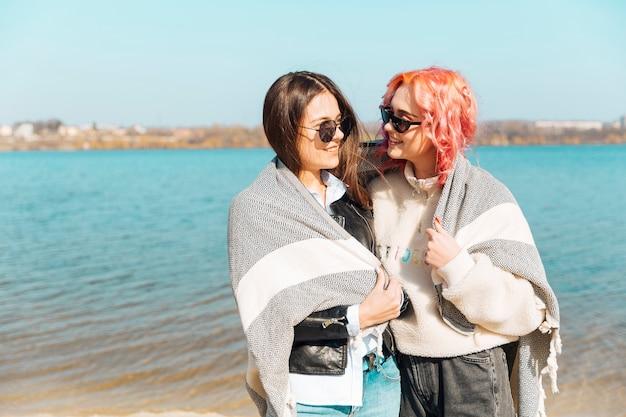 Mujeres jóvenes abrazándose y cubriéndose con manta