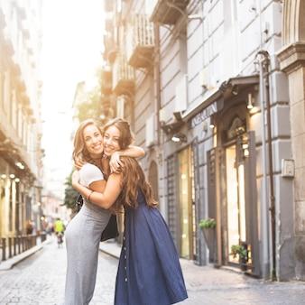 Mujeres jóvenes abrazándose de pie en la calle en la ciudad
