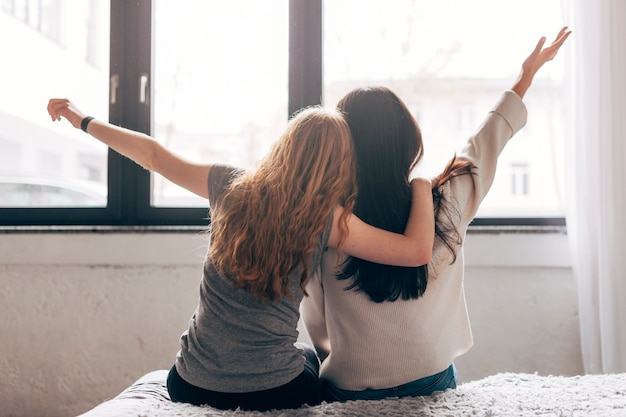 Mujeres jóvenes, abrazar, en cama