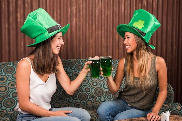 Mujeres jóvenes alegres chocando copas de bebida en el sofá en la habitación