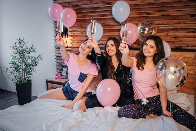 Las mujeres jovenes alegres se sientan en cama en sitio festivo. levantan vasos con champaña en el aire y los miran. niña sonriendo. tienen fiesta de pijamas.