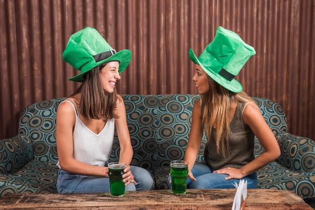 Mujeres jóvenes alegres con vasos de bebida en el sofá en la habitación