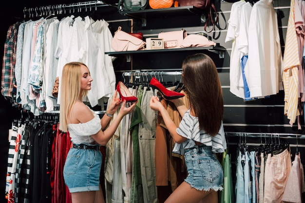 Mujeres jóvenes de ángulo bajo en la tienda de zapatos