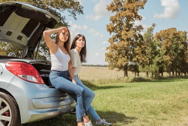 Mujeres jóvenes apoyadas contra su coche