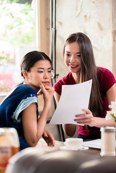 Mujeres jóvenes con archivos en una cafetería