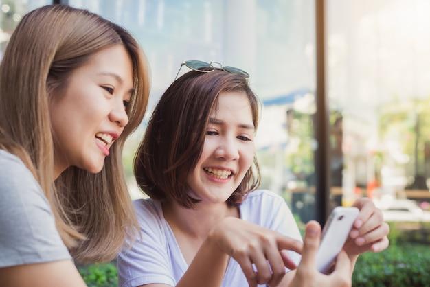 Mujeres jovenes asiáticas alegres que se sientan en café de consumición del café con los amigos y que hablan junto