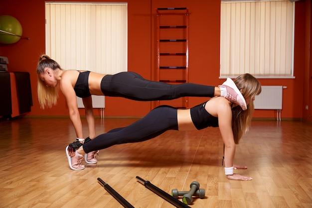 Las mujeres jóvenes atléticas un entrenamiento en el gimnasio.