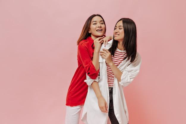 Las mujeres jóvenes atractivas se divierten en la pared rosa aislada