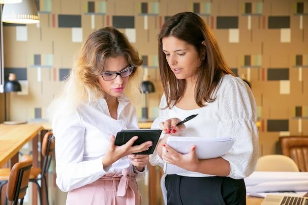 Mujeres jóvenes atractivas que buscan tendencias de diseño a través de una tableta y hablando