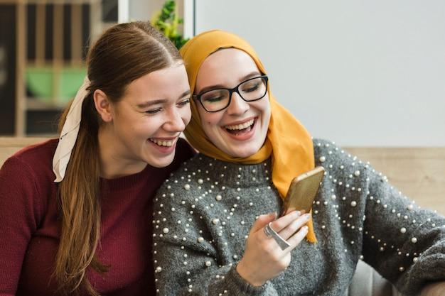 Mujeres jovenes atractivas que ríen juntas