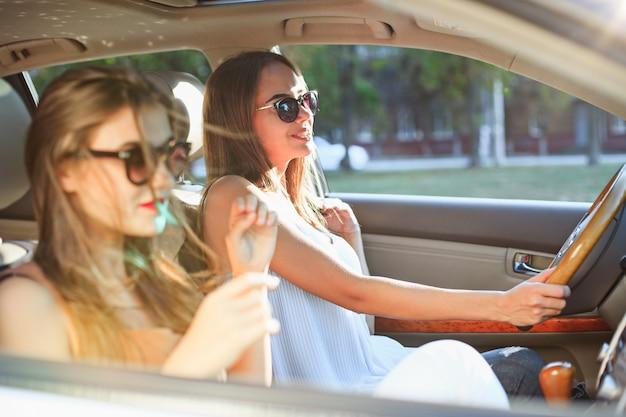 Las mujeres jóvenes en el auto sonriendo