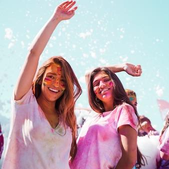 Mujeres jóvenes bailando y disfrutando del festival holi.