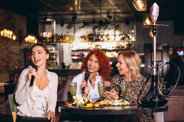 Mujeres jóvenes en un bar cantando karaoke