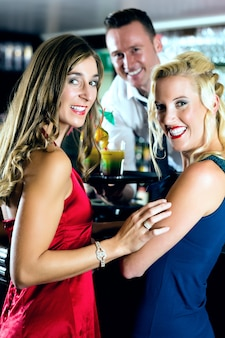 Mujeres jóvenes en el bar o club, el barman sirve cócteles