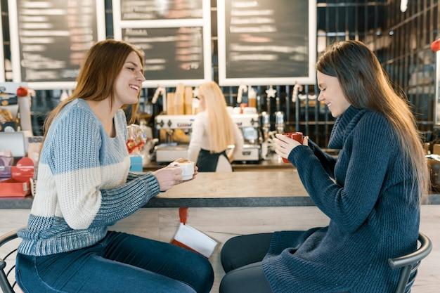 Las mujeres jóvenes bebiendo café en la cafetería, niñas sentadas cerca de la barra de bar