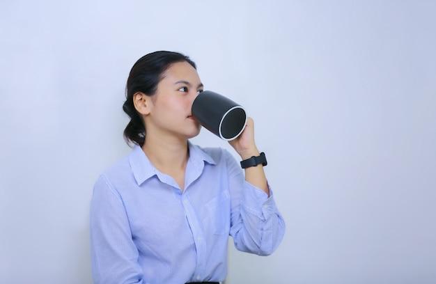 Las mujeres jóvenes bebiendo café contra el fondo blanco.