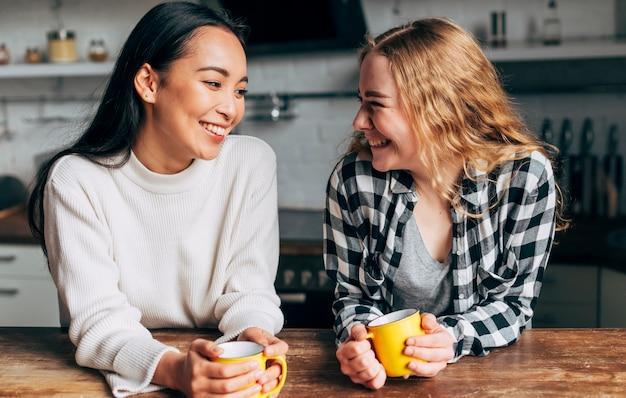 Mujeres jóvenes bebiendo té y sonriendo