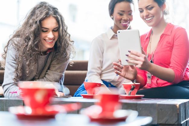 Mujeres jóvenes en café tomando selfie