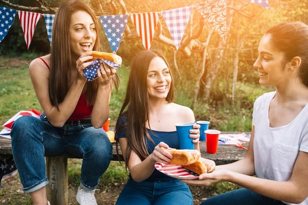 Mujeres jóvenes comiendo hot-dogs