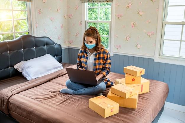Las mujeres jóvenes de compras en línea inician pequeños negocios en una caja de cartón en el trabajo.