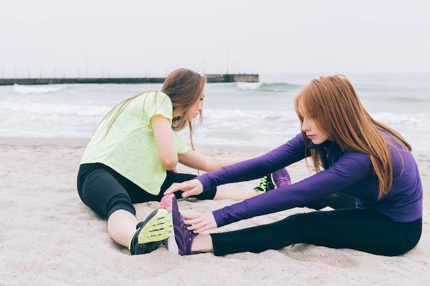 Mujeres jóvenes deportivas haciendo estiramientos en la playa en tiempo nublado
