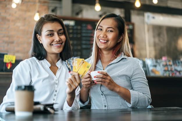 Las mujeres jóvenes disfrutan de las compras con tarjetas de crédito.