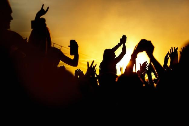 Las mujeres jóvenes disfrutan de un concierto de rock silueta en manos al atardecer al aire libre