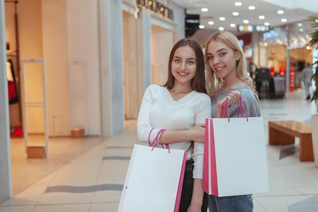 Mujeres jóvenes disfrutando de compras juntas en el centro comercial