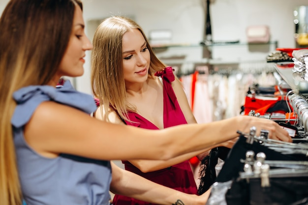 Mujeres jóvenes eligiendo ropa en un estante en una sala de exposición