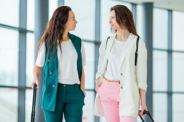 Mujeres jóvenes con equipaje en el aeropuerto internacional caminando con su equipaje. pasajeros de una aerolínea en un salón del aeropuerto esperando el avión de vuelo