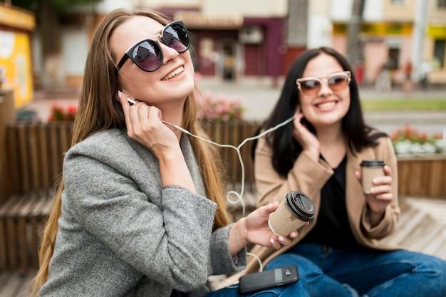 Mujeres jóvenes escuchando música a través de auriculares