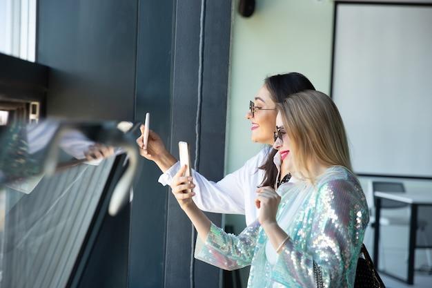 Mujeres jóvenes esperando la salida en el viajero del aeropuerto con estilo de vida de influenciadores de equipaje pequeño