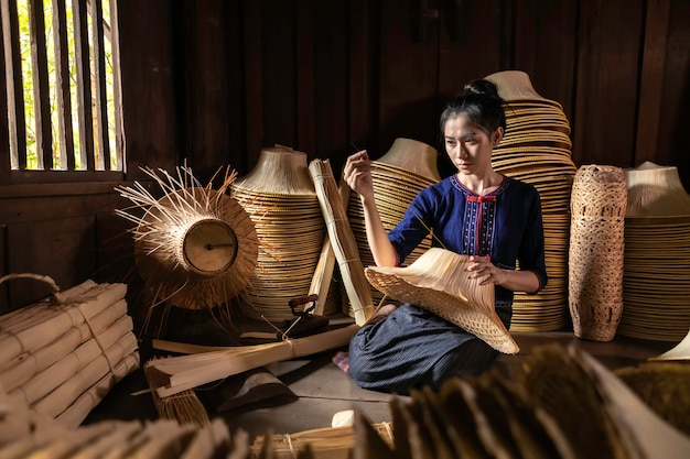 Las mujeres jóvenes están tejiendo en la canasta artesanal de campo de tailandia.