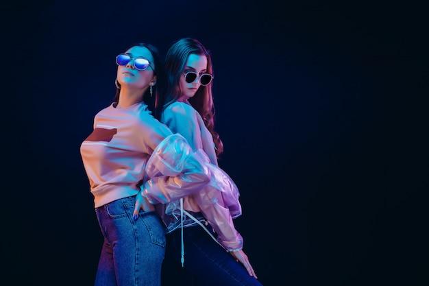 Mujeres jóvenes con estilo posando en luz de neón