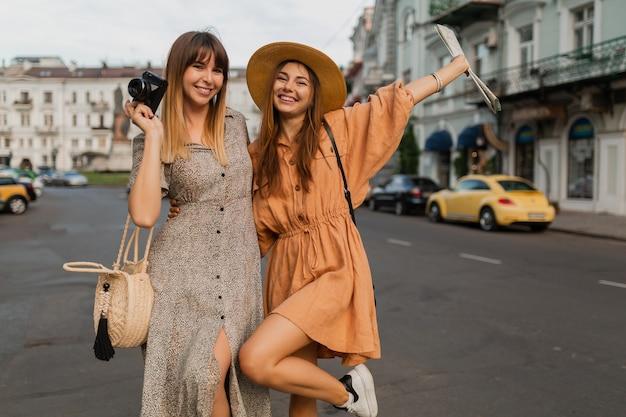 Mujeres jóvenes con estilo que viajan juntas en europa vestidas con vestidos y accesorios de moda de primavera