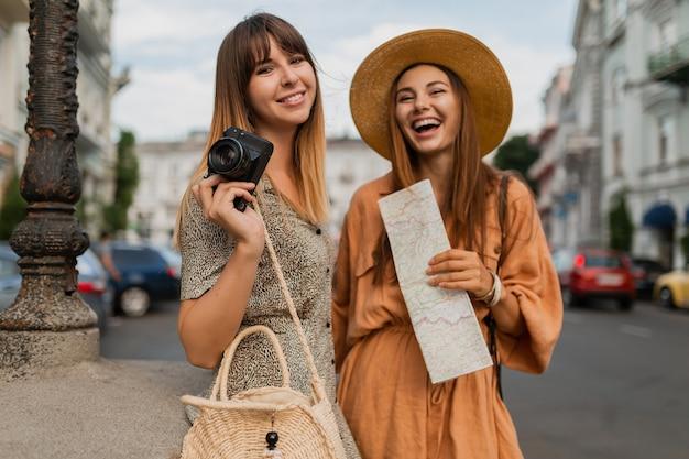 Mujeres jóvenes con estilo que viajan juntas vestidas con vestidos y accesorios de moda de primavera que se divierten tomando fotos en la cámara sosteniendo el mapa