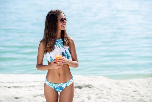 Mujeres jóvenes felices con cuerpo bronceado saludable en elegantes gafas de sol y bikini de moda disfrutando de vacaciones en la playa. chica con un cóctel en la playa