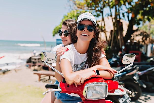 Mujeres jóvenes felices explorando la isla en motocicleta, con sombreros de verano, usando tableta y comprando música en línea contra el fondo de la ciudad, isla exótica, viaje, vacaciones de verano