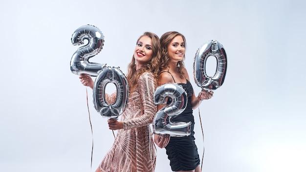 Mujeres jóvenes felices con globos metálicos 2020 en blanco.