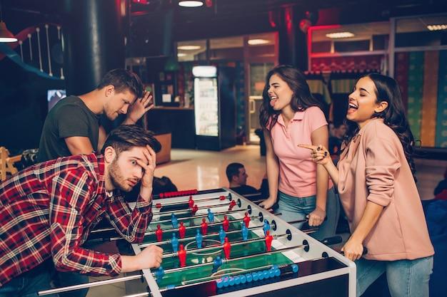 Las mujeres jóvenes felices miran a los hombres y se encogen. ellos ganan el juego. chicos lo perdieron. ellos decepcionaron. los jóvenes están parados en la sala de juego.