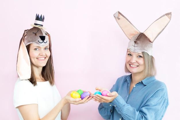 Las mujeres jóvenes felices en orejas de conejo están sosteniendo coloridos huevos de pascua sobre fondo rosa claro