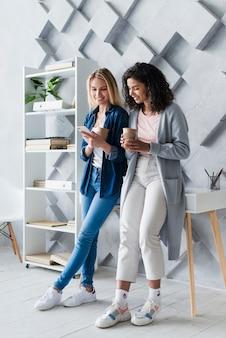 Mujeres jovenes felices que beben el café en oficina