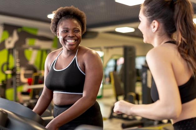 Mujeres jóvenes en el gimnasio entrenando juntas