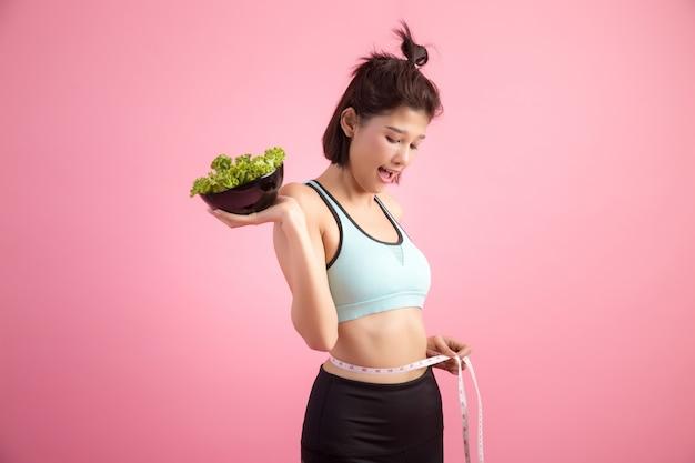 A las mujeres jóvenes les gusta comer verduras en una rosa.