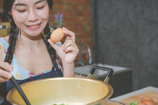 Las mujeres jóvenes hacen bocadillos en la cocina.