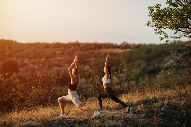Mujeres jóvenes haciendo ejercicios en la montaña durante la puesta de sol. yoga, fitness y estilo de vida saludable.