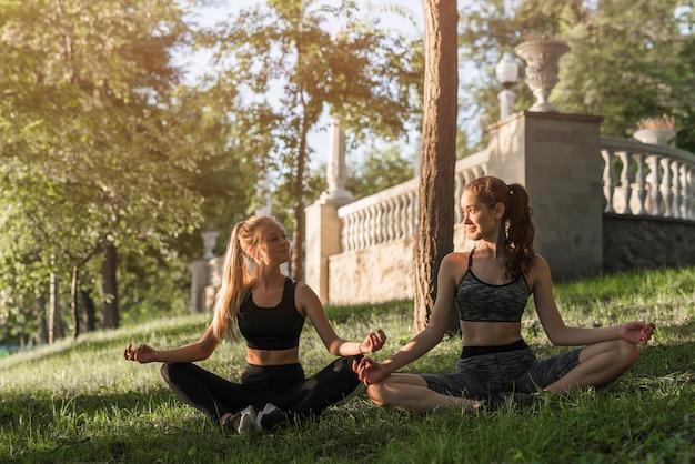 Mujeres jóvenes haciendo yoga en el parque